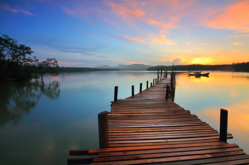 ponton s'élançant au soleil couchant sur une lagune apaisée